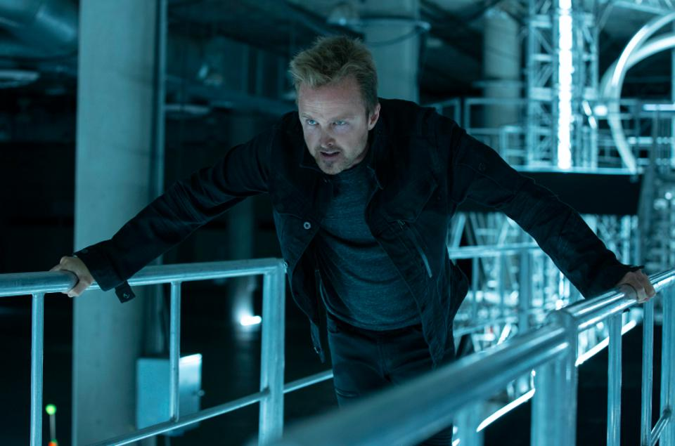 Aaron Paul portrays Caleb Nichols, who is at the center of the race to save or destroy humankind.