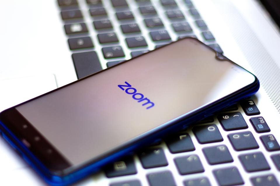 Smartphone displaying Zoom logo sits on top of a laptop keyboard