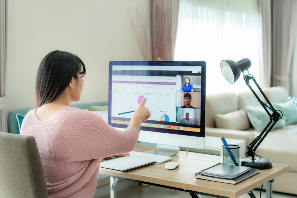Woman in living room pointing at graphs on screen, in video conferencing call with others