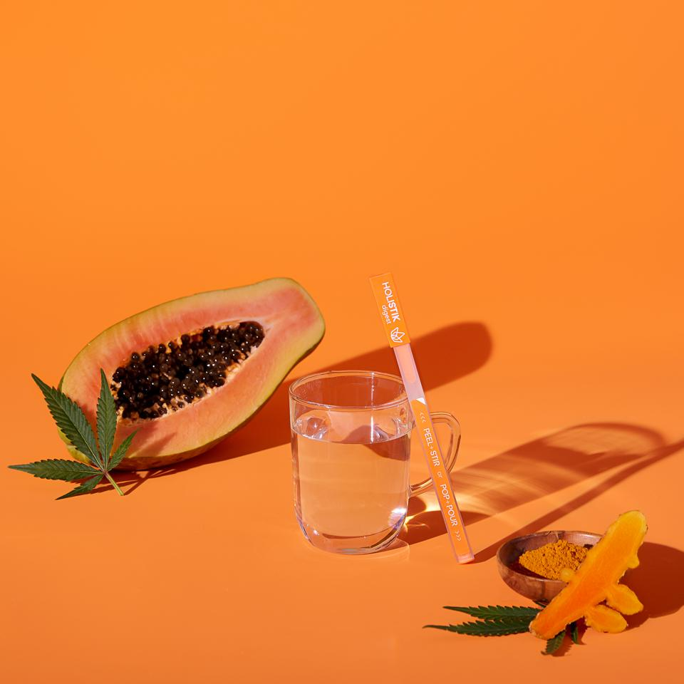 HOLISTIK concentrate and a ripe mango slice with a cannabis leaf and a glass of cool water