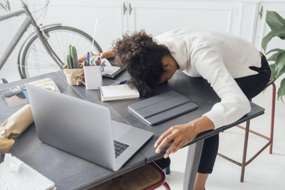 Tired freelancer sleeping on her deak
