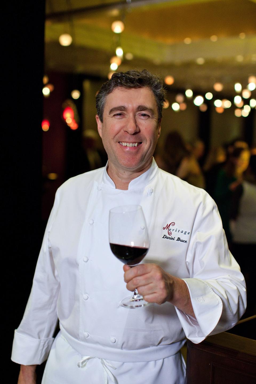 Chef Daniel Bruce holding a glass of wine.