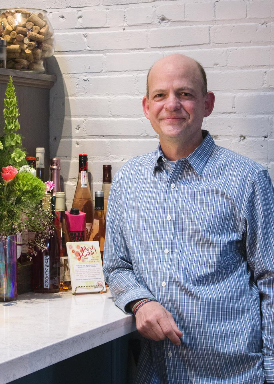 Man leaning on a counter with wine bottles.