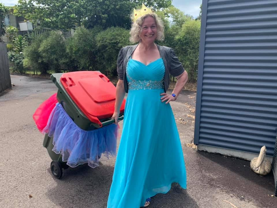 A woman is dressed up as a princess as she takes her rubbish bin out.
