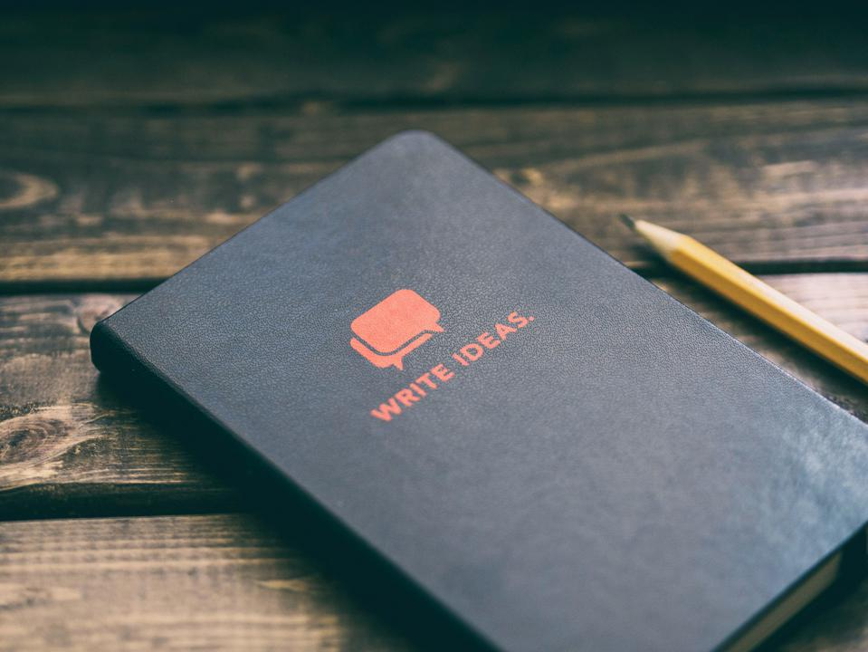 A black notebook with the moniker 'write ideas' on it, next to a pencil.