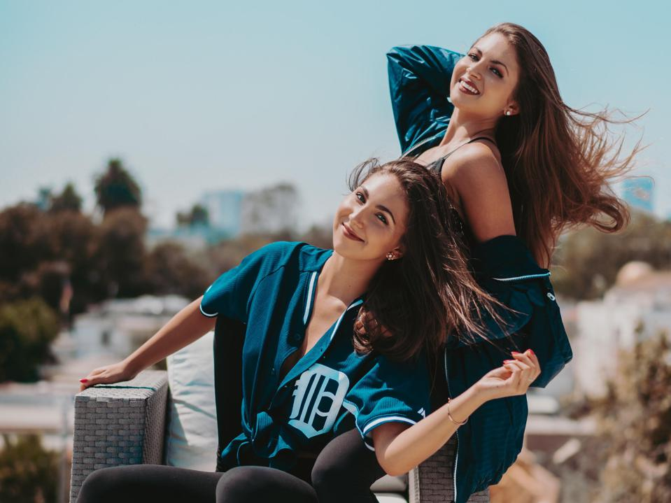 The Wilking Sisters pose in baseball jerseys, Downtown LA skyline in background