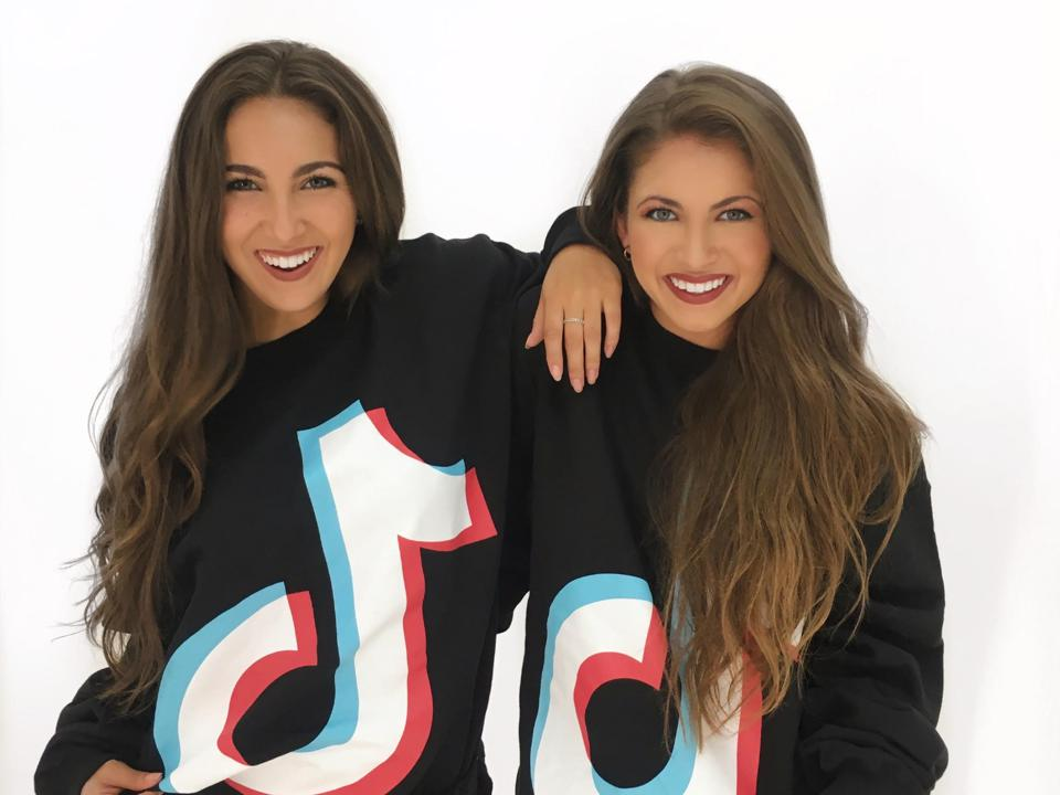 The Wilking Sisters pose in TikTok sweatshirt.