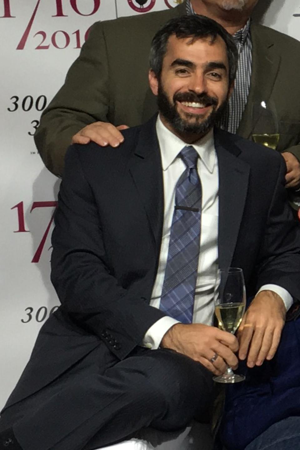 Bearded man sitting with a glass of wine.