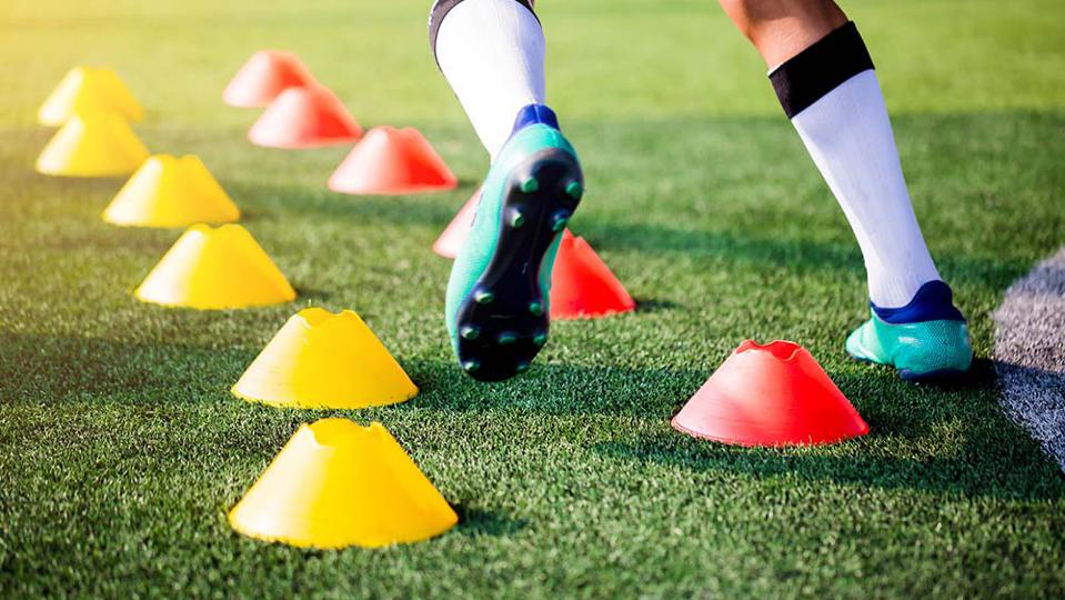 A young soccer player navigating through pylons for an agility drill.