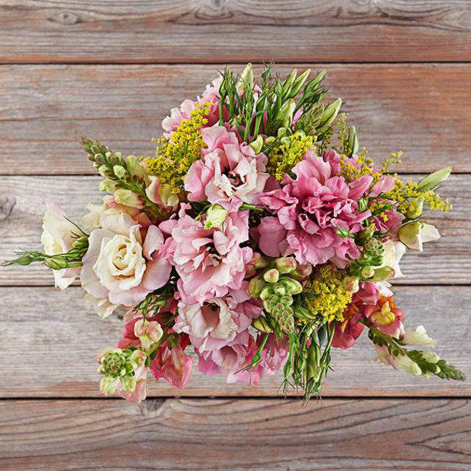 A lush bouquet of flowers featuring pink rose-like flowers and yellow snap dragons.