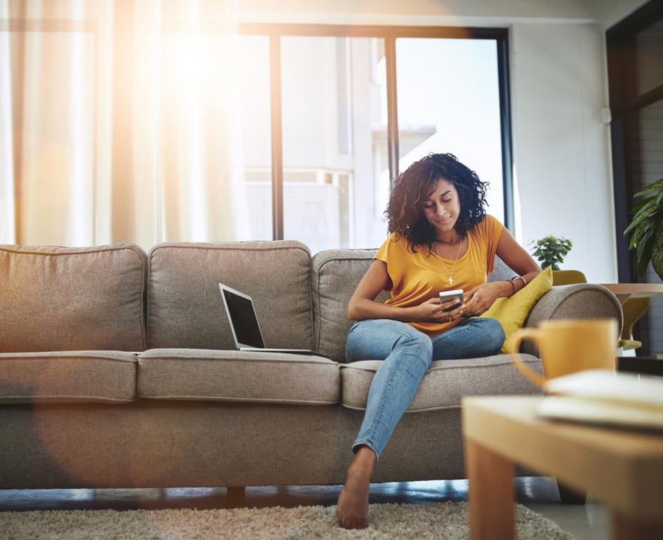 Woman wearing a yellow shirt and jeans, sitting on a couch with light shining in from the window behind her.