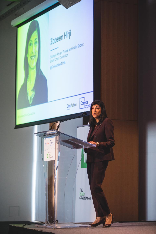 Lady, Zabeen Hirji,  speaking at a microphone,