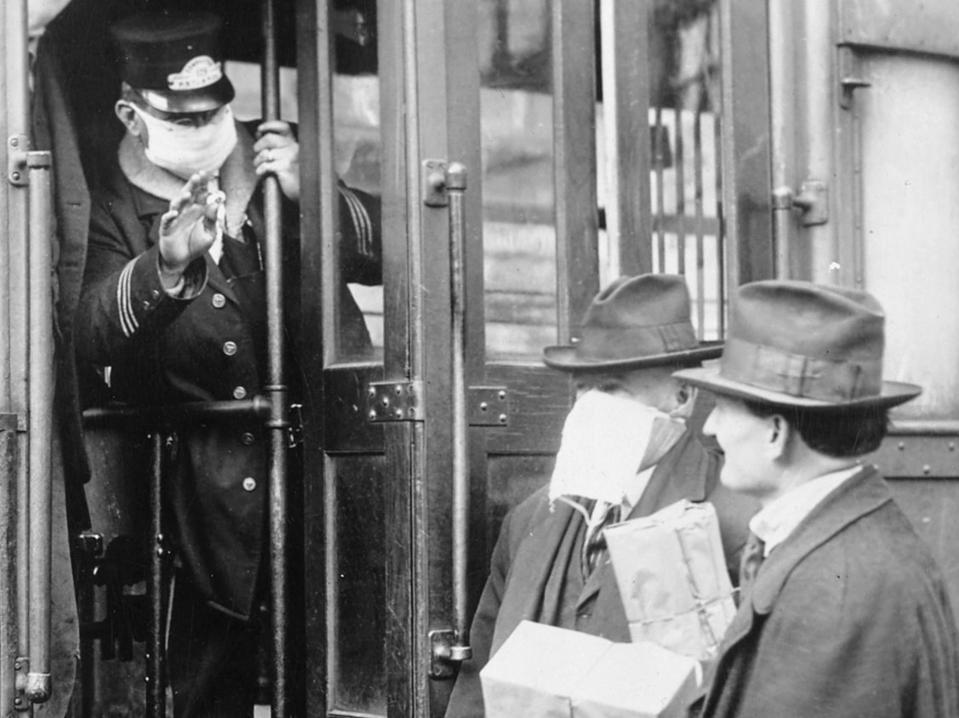 Photo of a masked trolley operator and two men in hats, one in a mask and one without one.