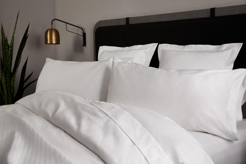 white hotel bedding with wall lamp and plant
