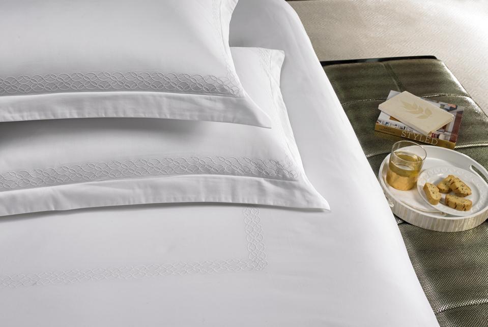 white hotel bedding with lattice trim