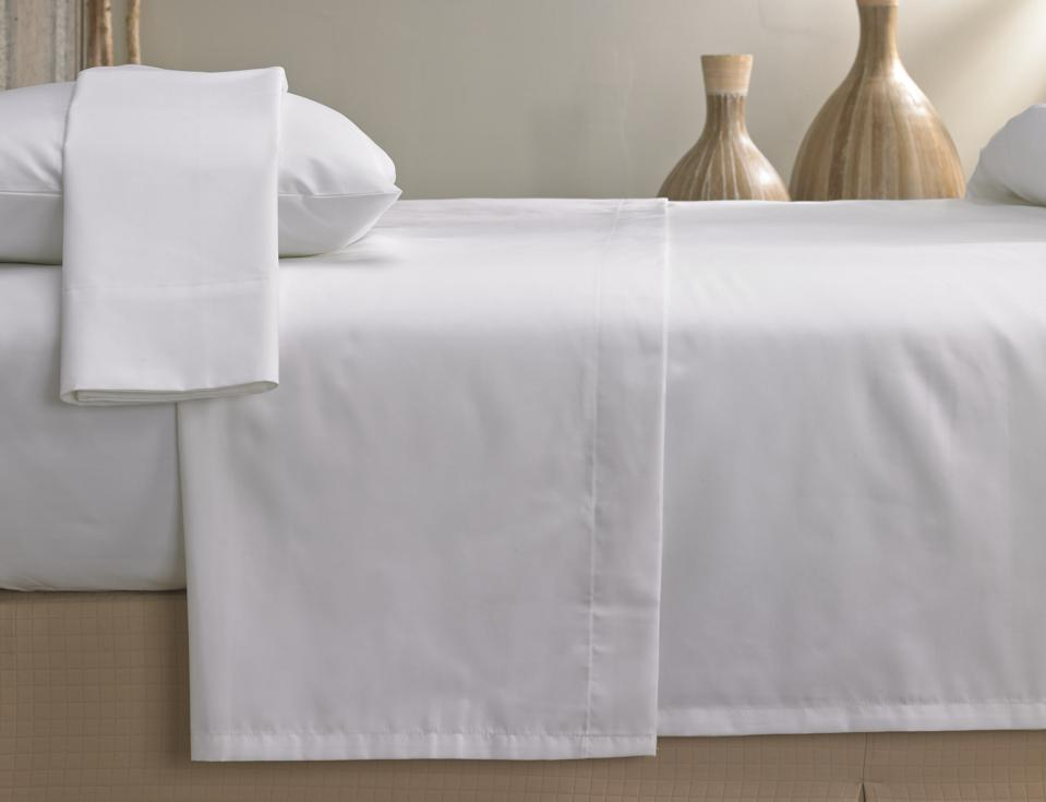 white sheets on beige bed with beige ceramics