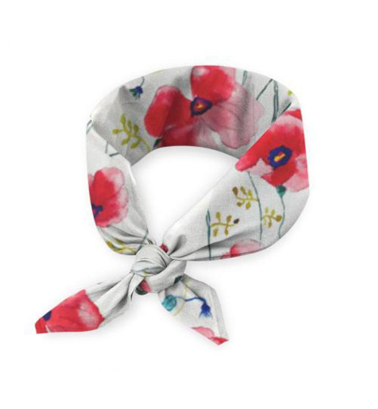 A poppy print scarf rolled up and tied
