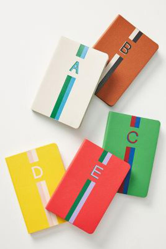 Clare V. for Anthropologie notebooks each with a different letter and a two tone stripe