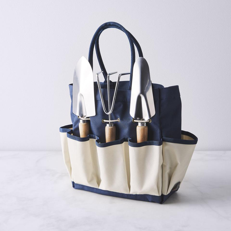 Canvas tote with navy interior and side pockets holding garden tools