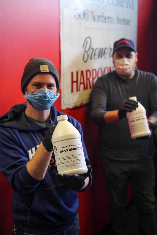 Men wearing masks holding hand sanitizer