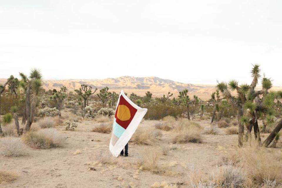 Woman holds blanket with red, blue and grey shapes in the desert.