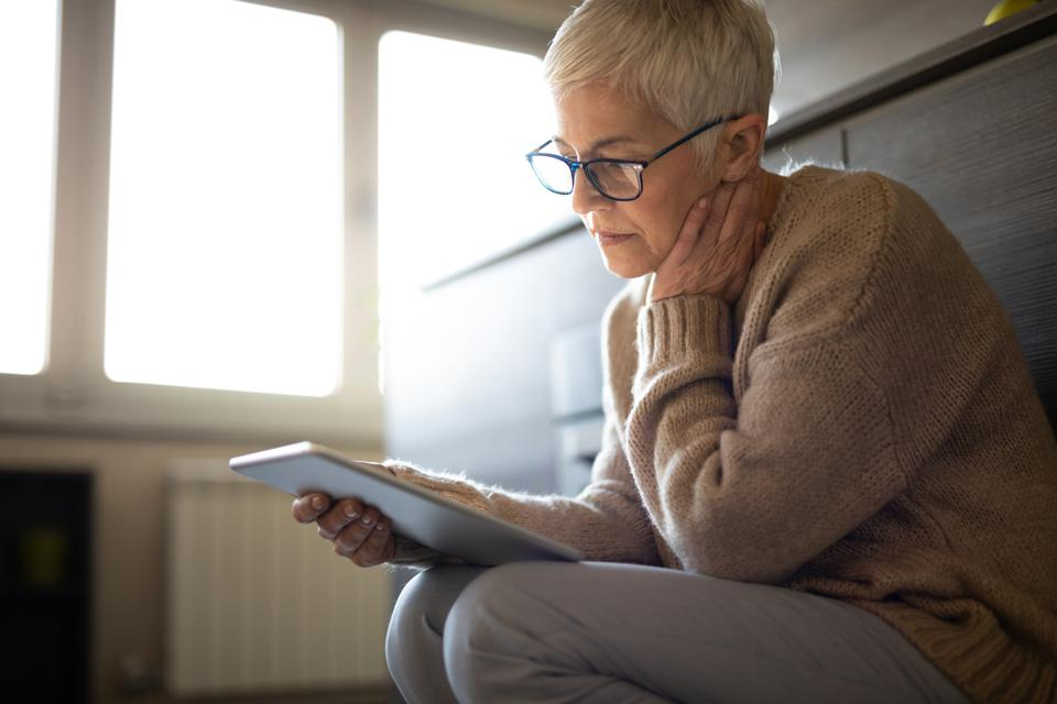Worried senior woman reading an e-mail on tablet