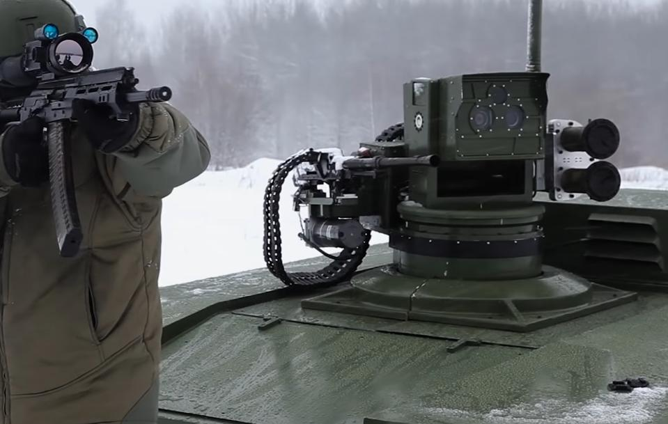 A soldier with a rifle and a robot tank.