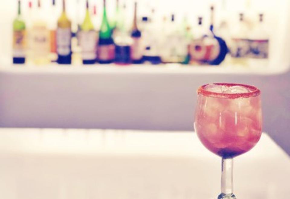 Mezcal margarita with bar backdrop.