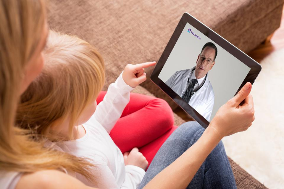 Mother and child doing virtual doctor visit on tablet device.