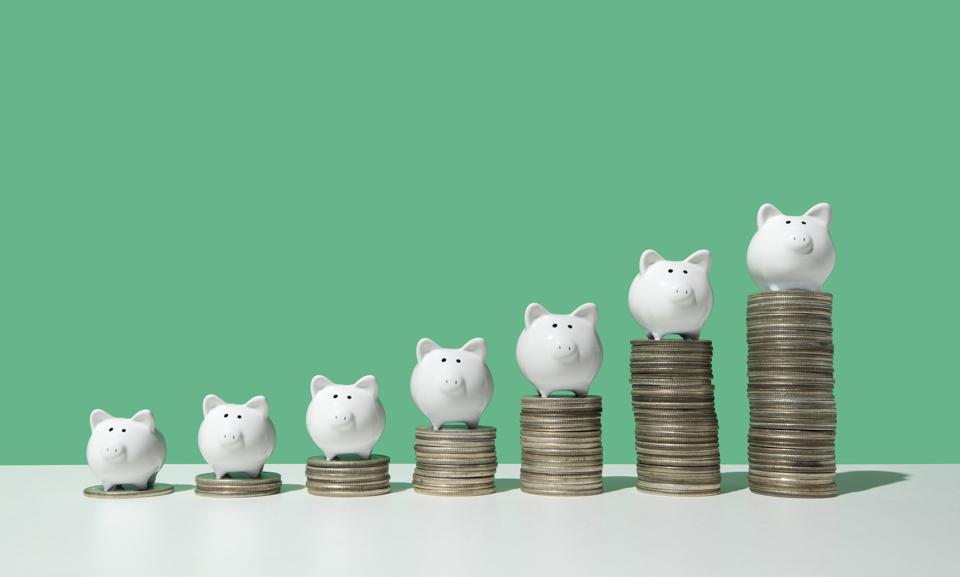 Little piggy banks on ascending stacks of coins