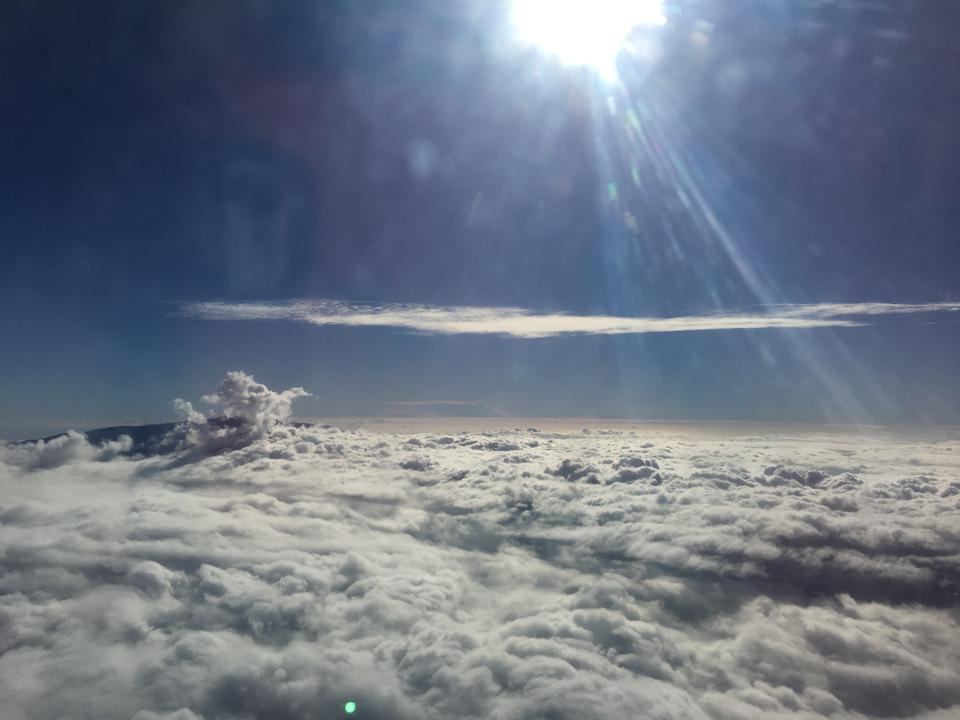 flying over the clouds with clear blue sky and brilliant shining sun