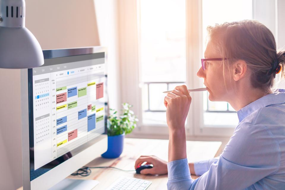 Person checking schedule on computer.
