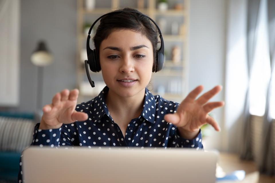Indian woman teacher wear wireless headset video calling on laptop