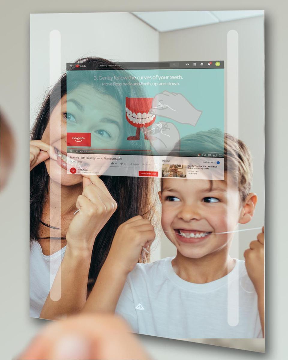 The internet screen helps the mother teach her son to clean his teeth with dental floss.