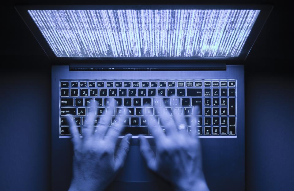 Blurred hands are typing on a laptop computer in the dark with illuminated keyboard