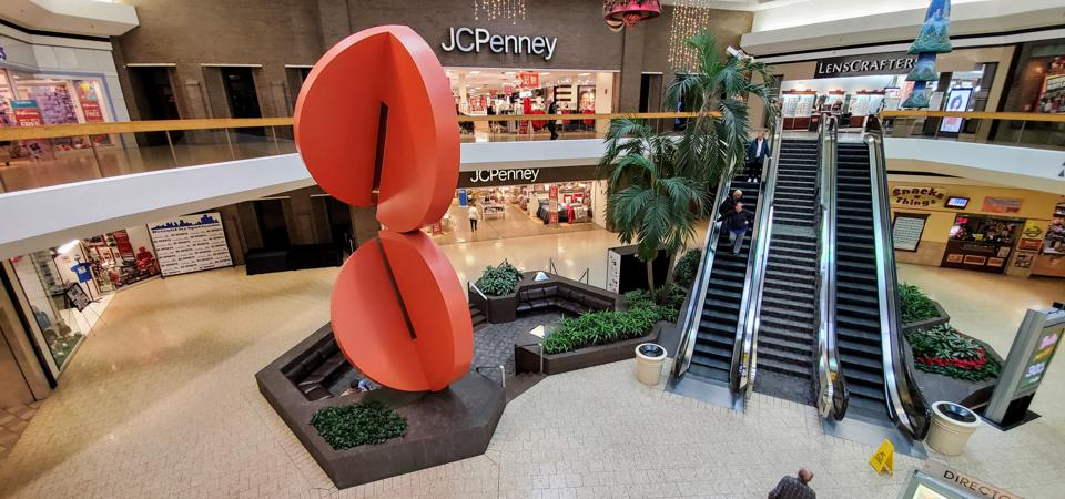 A inside courtyard at Lakeside Mall in Sterling Heights, MI. showing a JC Penney store, escalators, and other stores.