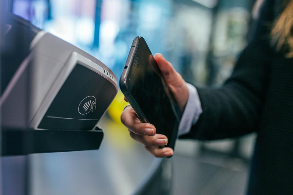 A person holding their phone to a ″contactless″ payment terminal
