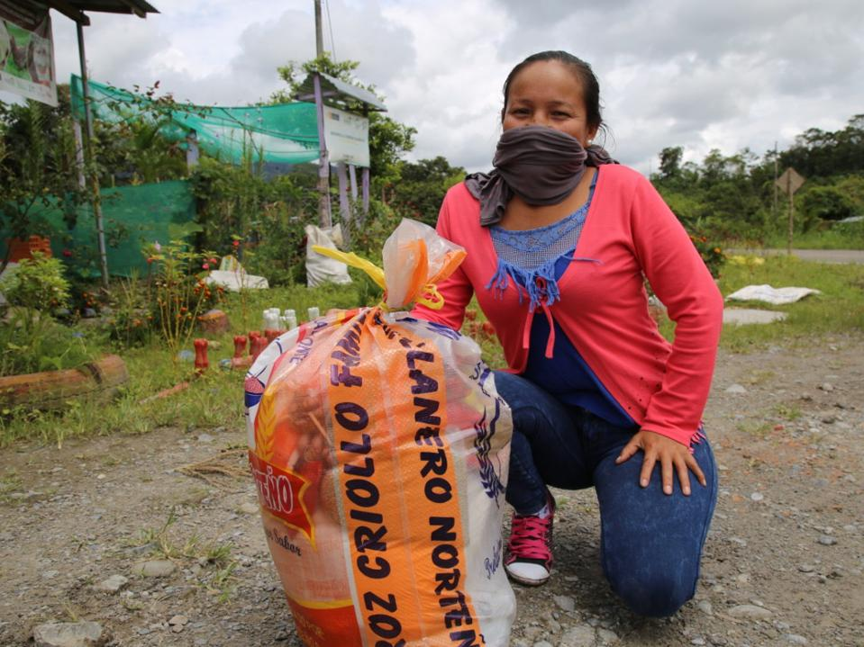 A member of a Peruvian coffee coop receives a bag of food during COVID19.