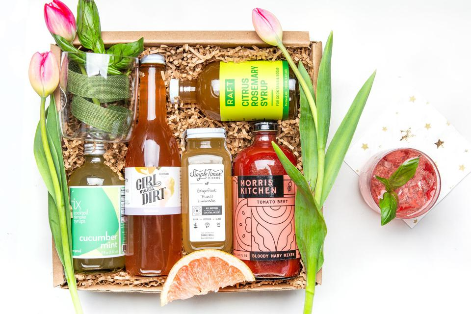 A gift basket filled with artisanal cocktail mixers, decorated with tulips
