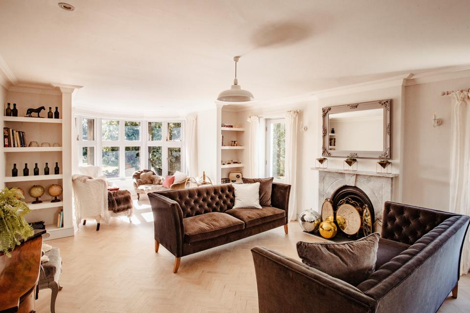 A sitting room with velvet sofas, an open fireplace and a large bay window