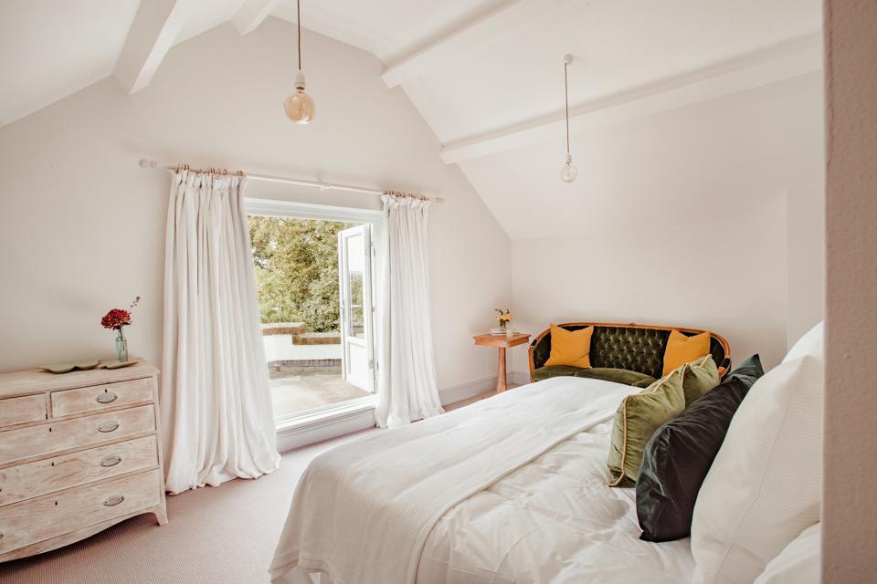 Master bedroom with white walls and pitched ceiling opening onto a balcony