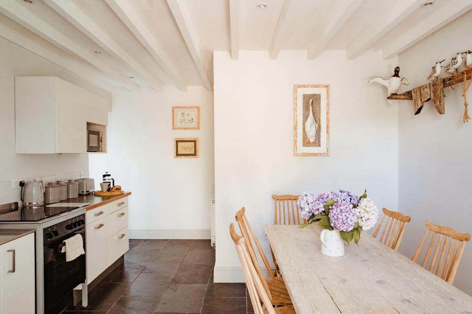 Beamed ceiling and wooden dining table feature in the cottage's kitchen