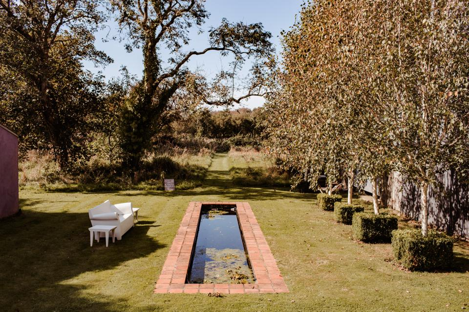 A rectangular brick pond, lawns, and meadow areas