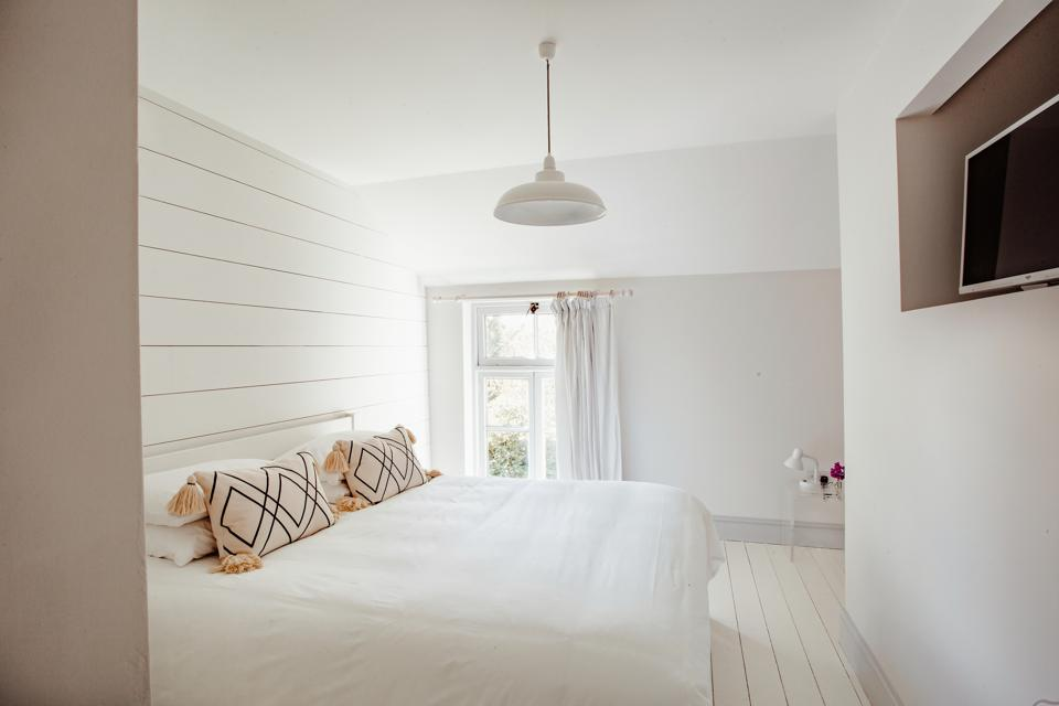 A bedroom with an all-white interior