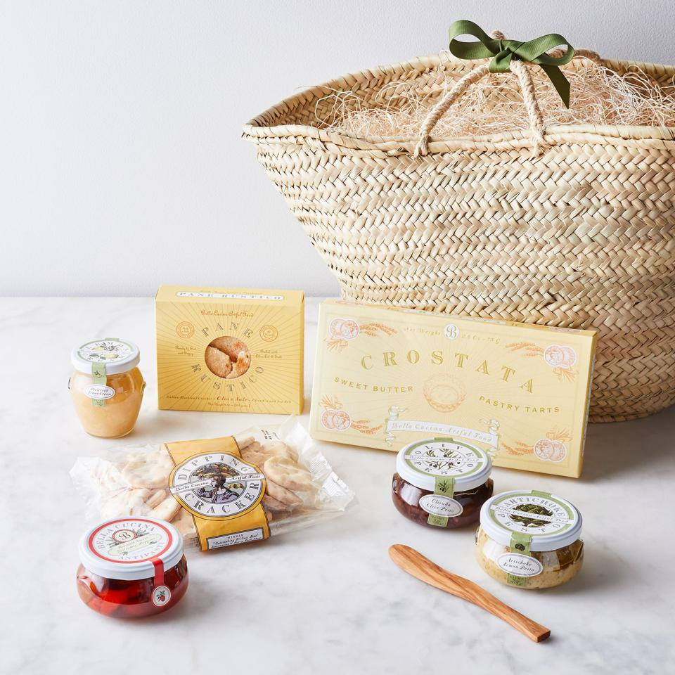 A rustic basket bag with Italian antipasta goodies in jars and boxes