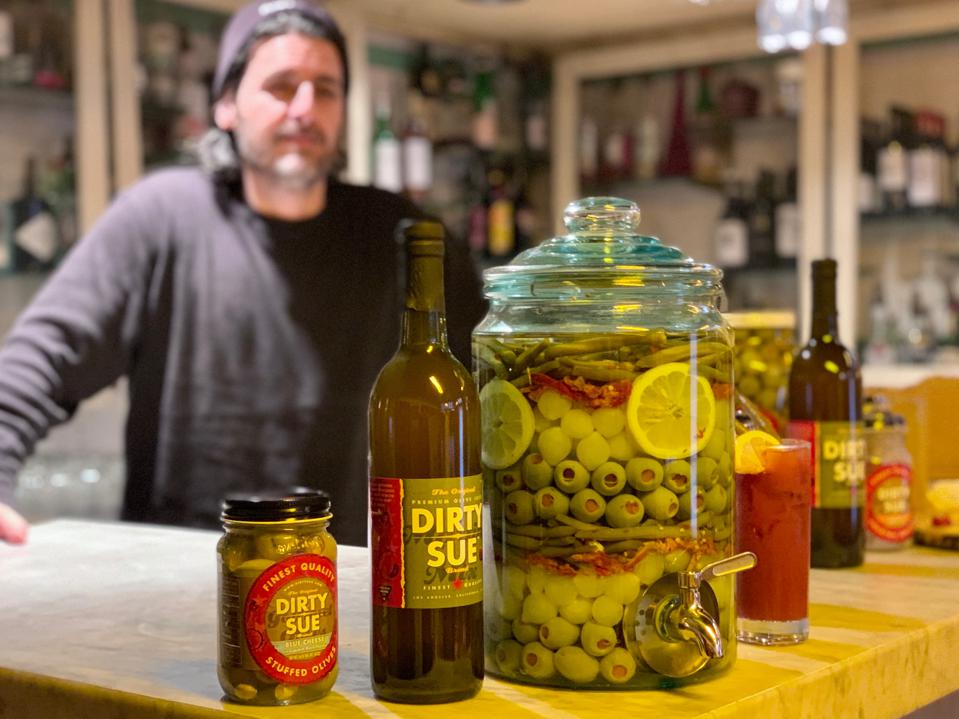 Counter with a jar full of olives and peppers. Bottles of Dirty Sue olive juice mixer