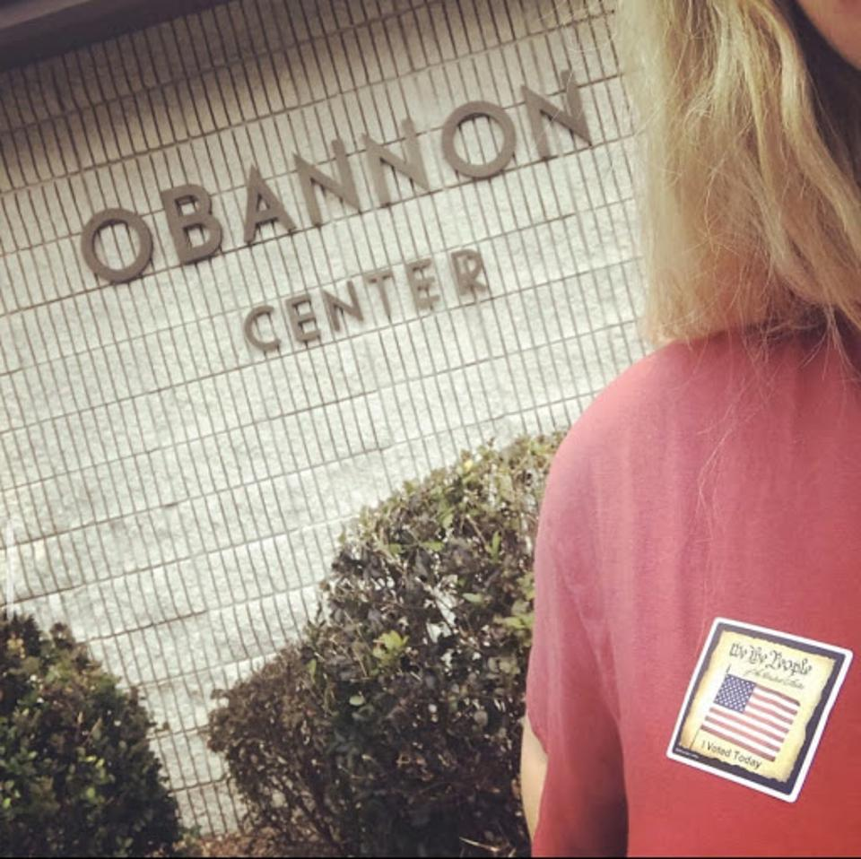 Kristen posing with her first voting sticker outside the polling place.