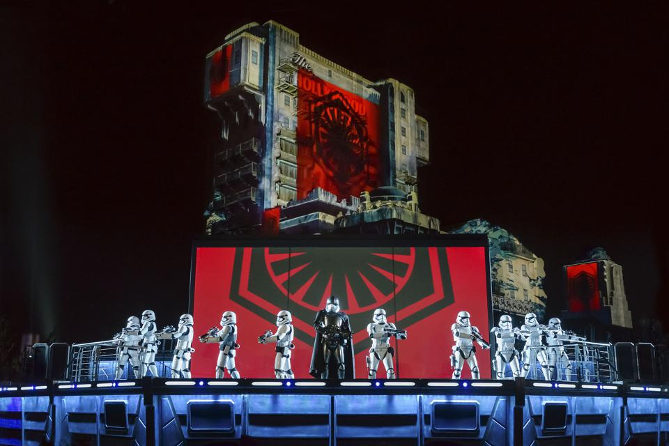 A screen at the foot of the stage shows scenes from the Star Wars movies whilst costumed characters act in front of it