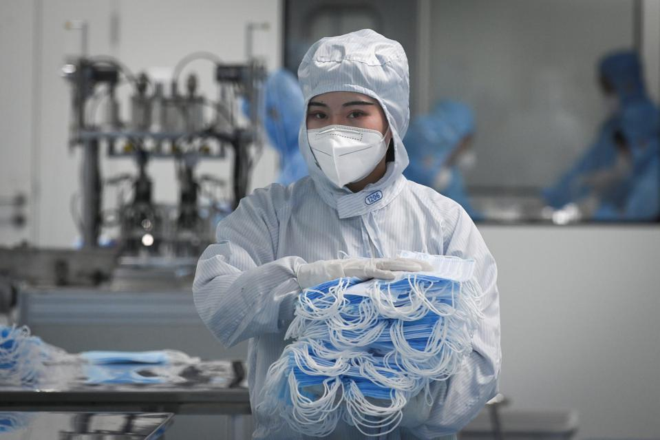 A worker wearing a protective suit holds masks