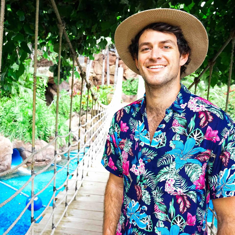 Haisfield stands on a rope bridge in a straw hat with a bright colored shirt.
